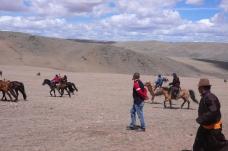 Mongolian men on horses.