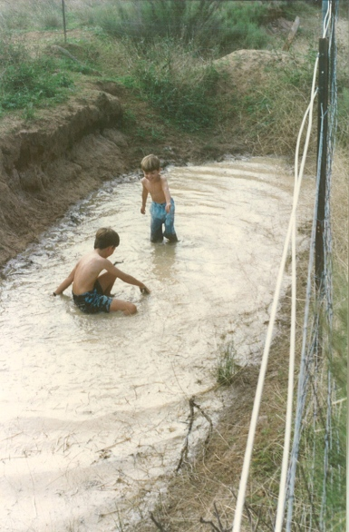 Playing in the erosion gully on our farm